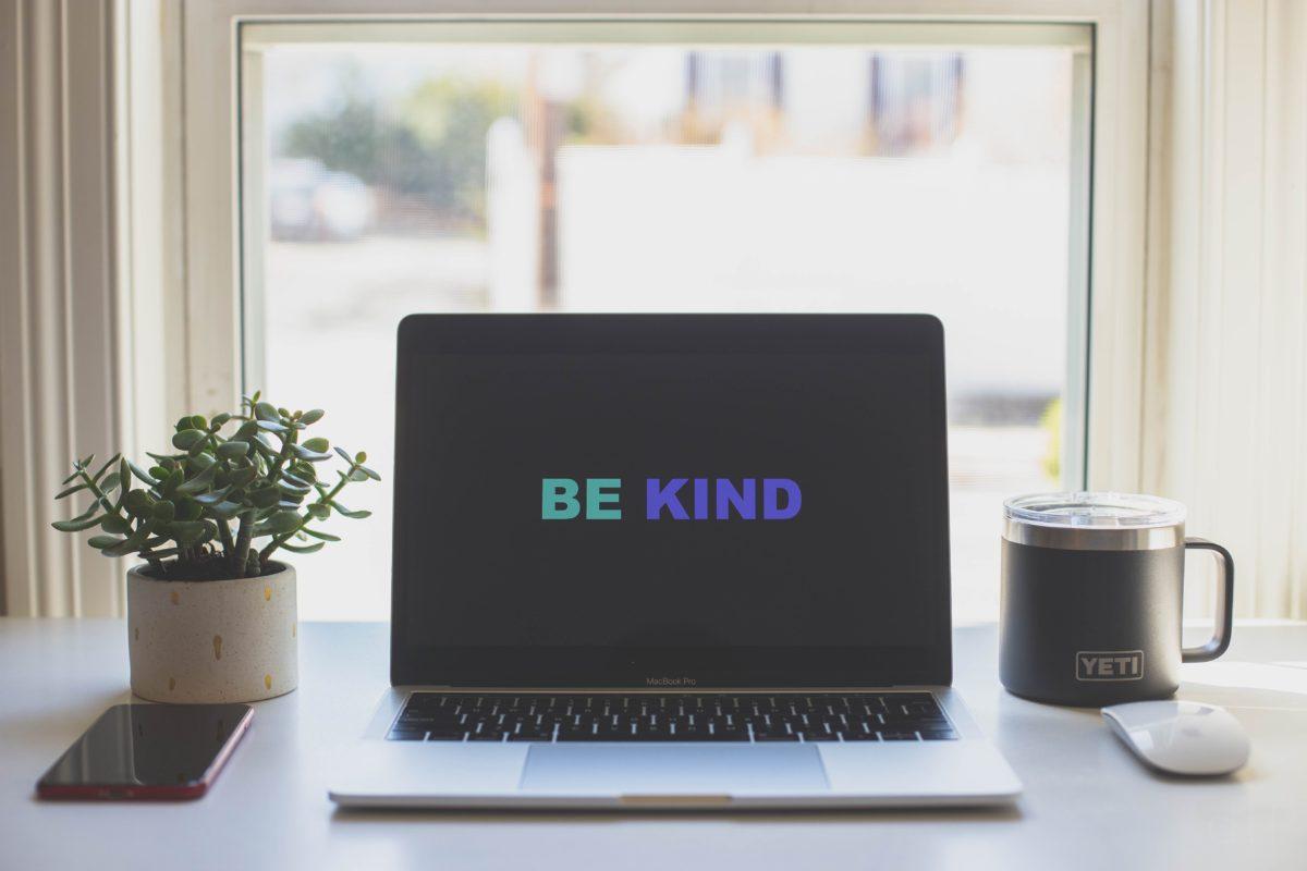 Be Kind on a laptop wallpaper next to a yeti mug